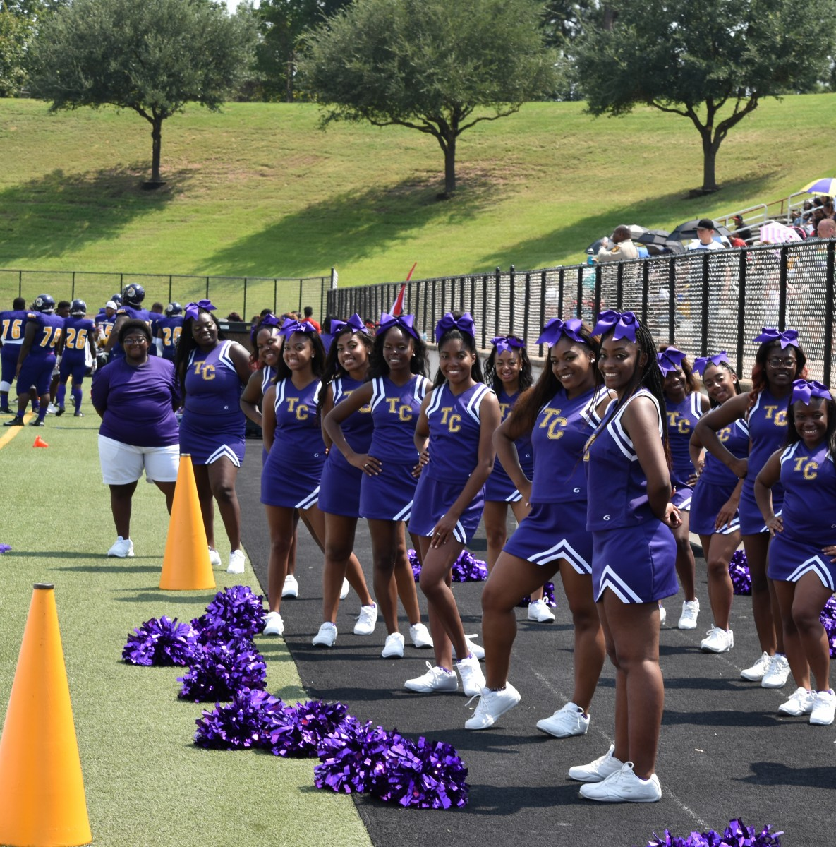 Texas College Cheerleaders in purple uniforms at a football game.